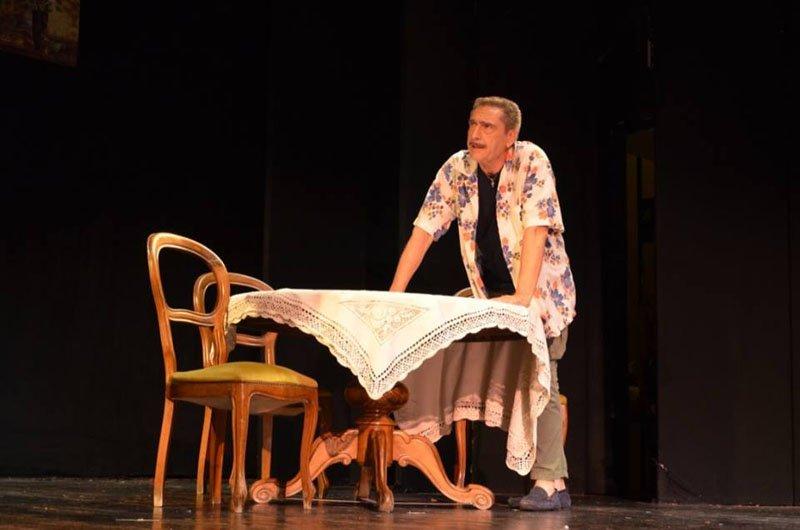 attore mentre recita con le mani appoggiate su un tavolo