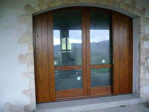 una porta finestra in legno con delle persiane