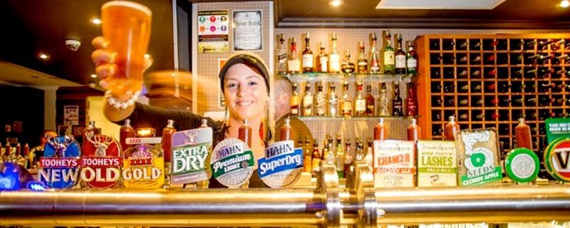 woman serving behind bar