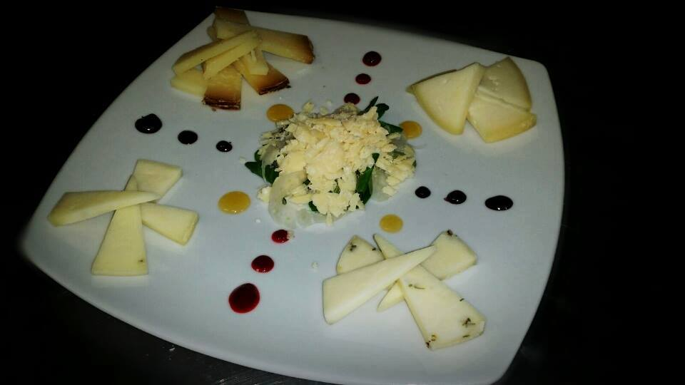 A square plate with slices of different types of cheeses and drops of sauces