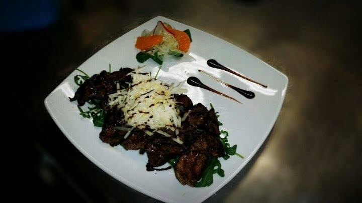 Un piatto a base di carne ai ferri, insalata, verdura e decorazione con aceto balsamico