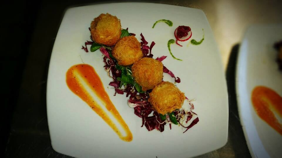 fried mozzarella, red salad and orange sauce in a square dish