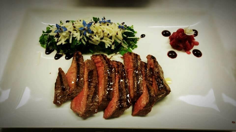 Tagliata di carne al sangue, Insalata decorata con dei fiori blu e salsa rosso nel piatto rettangolare