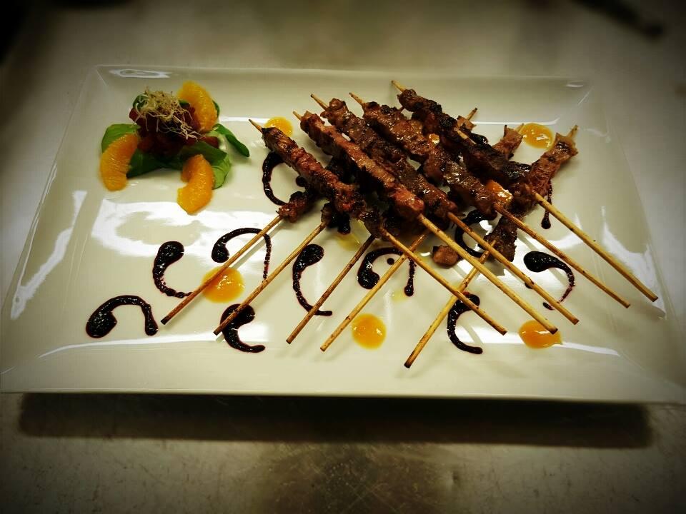 Un piatto con spiedini di carne disposti a formare una griglia, decorazione di aceto balsamico e fette di arancia sul lato sinistro