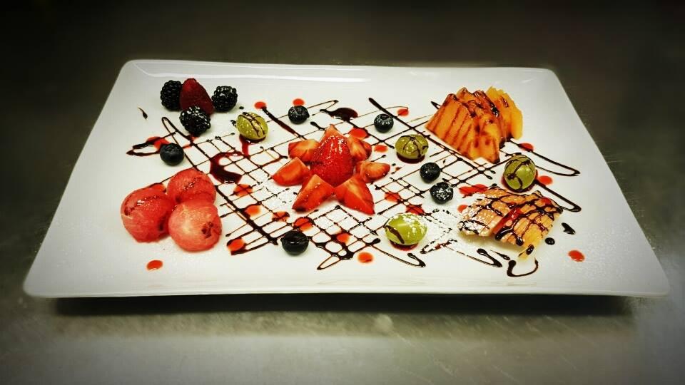 Frutta disposto in un piatto decorativo e decorazioni con una salsa che forma una rete