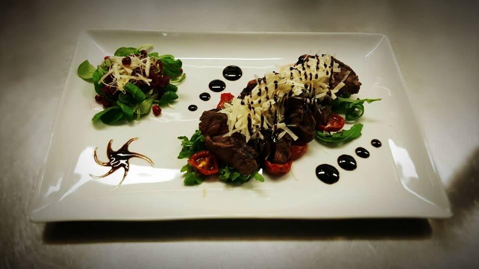Un piatto con arrosto, insalata ,pomodorini e decorazione con aceto balsamico