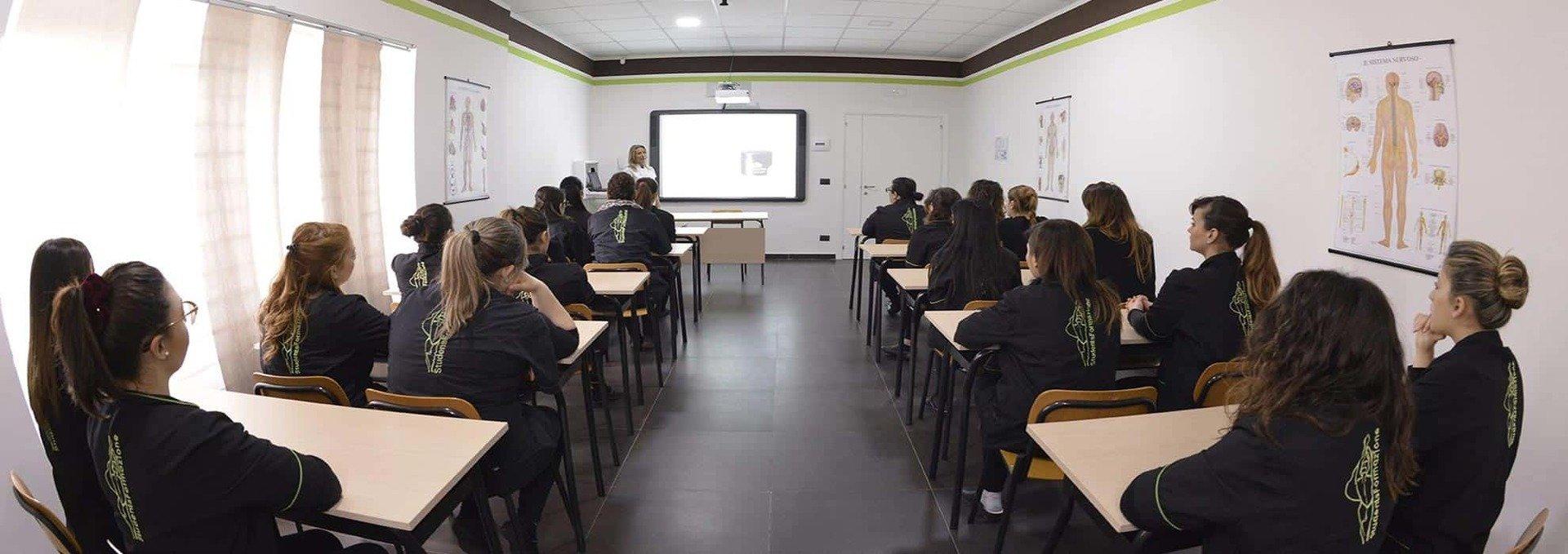 un'aula con delle ragazze in uniforme nere