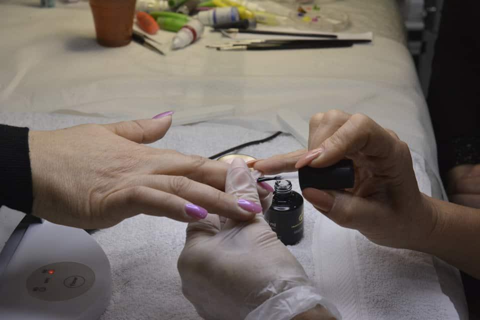 una mano mentre mette dello smalto di color viola sulle unghie di una donna