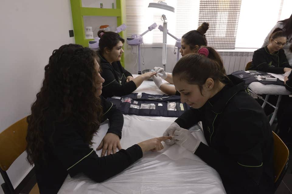 delle ragazze sedute al tavolo mentre fanno delle manicure