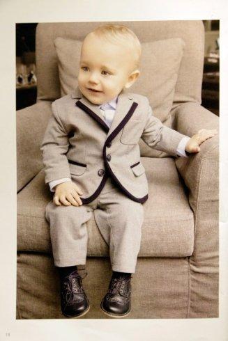 un bambino con un completo di color grigio