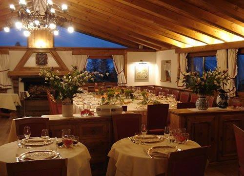 sala ristoro con tavoli apparecchiati e fiori sopra