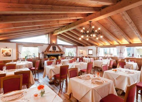 vista laterale del ristorante con lampadario accesso e travi a vista
