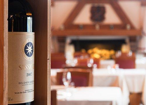 primo piano di una bottiglia di vino con tavoli apparecchiati sullo sfondo