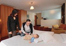 un neonato sdraiato su un letto e i genitori in piedi in una stanza