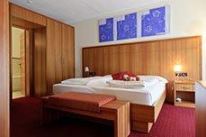 una camera con un letto matrimoniale e due comodini in legno