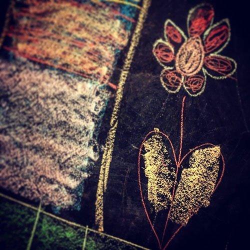 Fiore e cuore disegnati con gessetti di colori