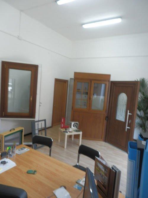 una scrivania con delle sedie, delle porte e delle finestre