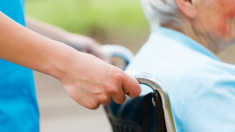 Elderly person being pushed in a wheel chair