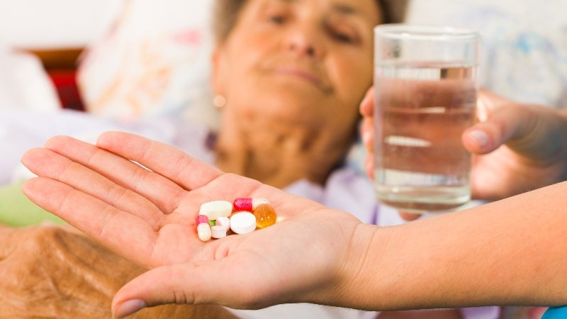 Nurse giving old woman a handful of pills