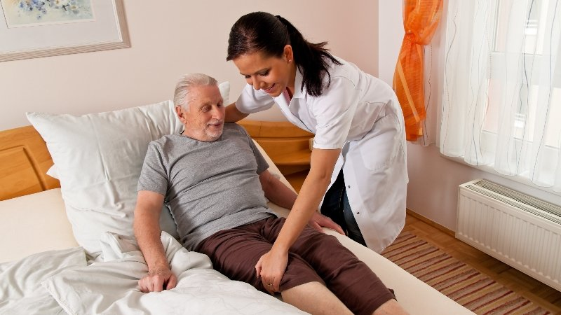 Elderly person being helped into bed