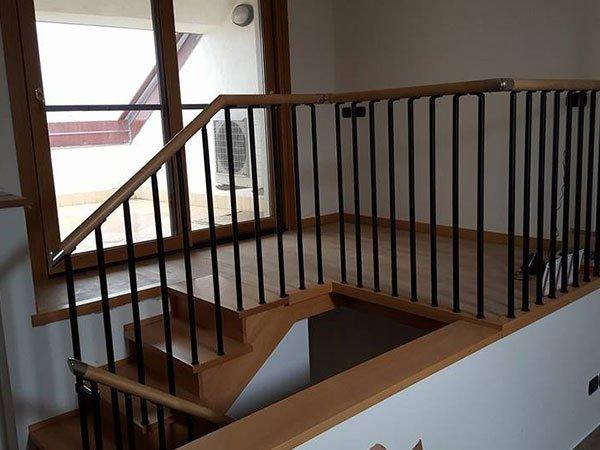 delle scale in legno con i parapetti di color nero