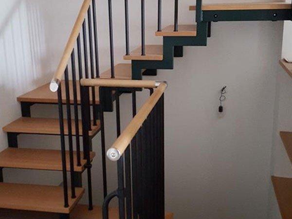 delle scale in legno con corrimano di color marrone in metallo