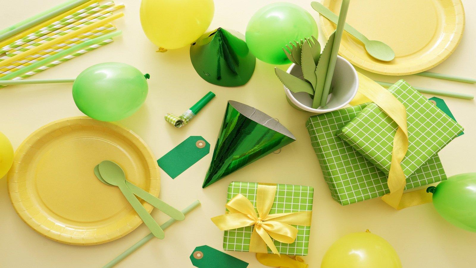 Piatti, posate e paglie in plastica verde e gialla