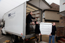 A white chest of drawers being loaded onto a removal van
