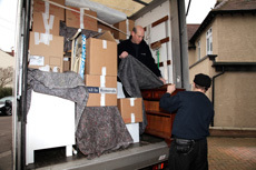 Objects on a van being covered with protective sheeting