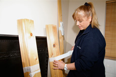 A lady taping some planks of wood together