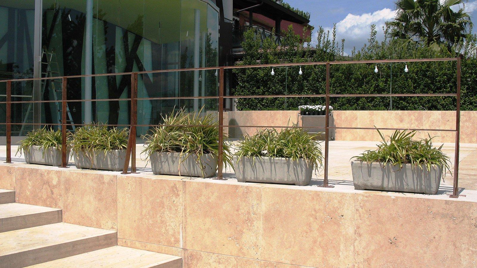 una terrazza davanti a un edificio con una ringhiera in metallo