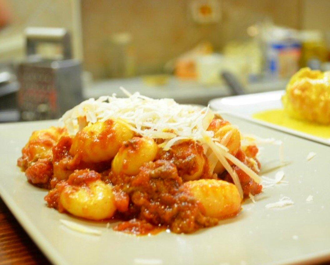 vista laterale gnocchi di patate col ragu e formaggio grattugiato