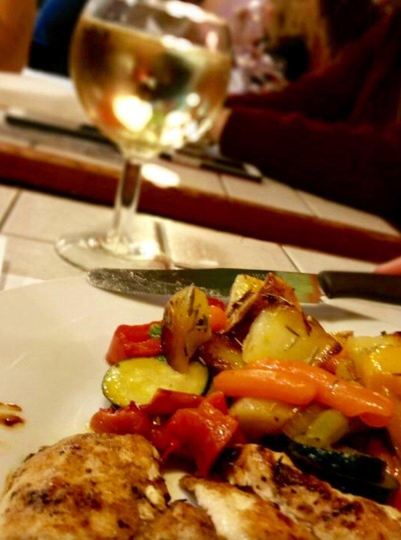 pesce con verdure grigliate e bicchiere di vino