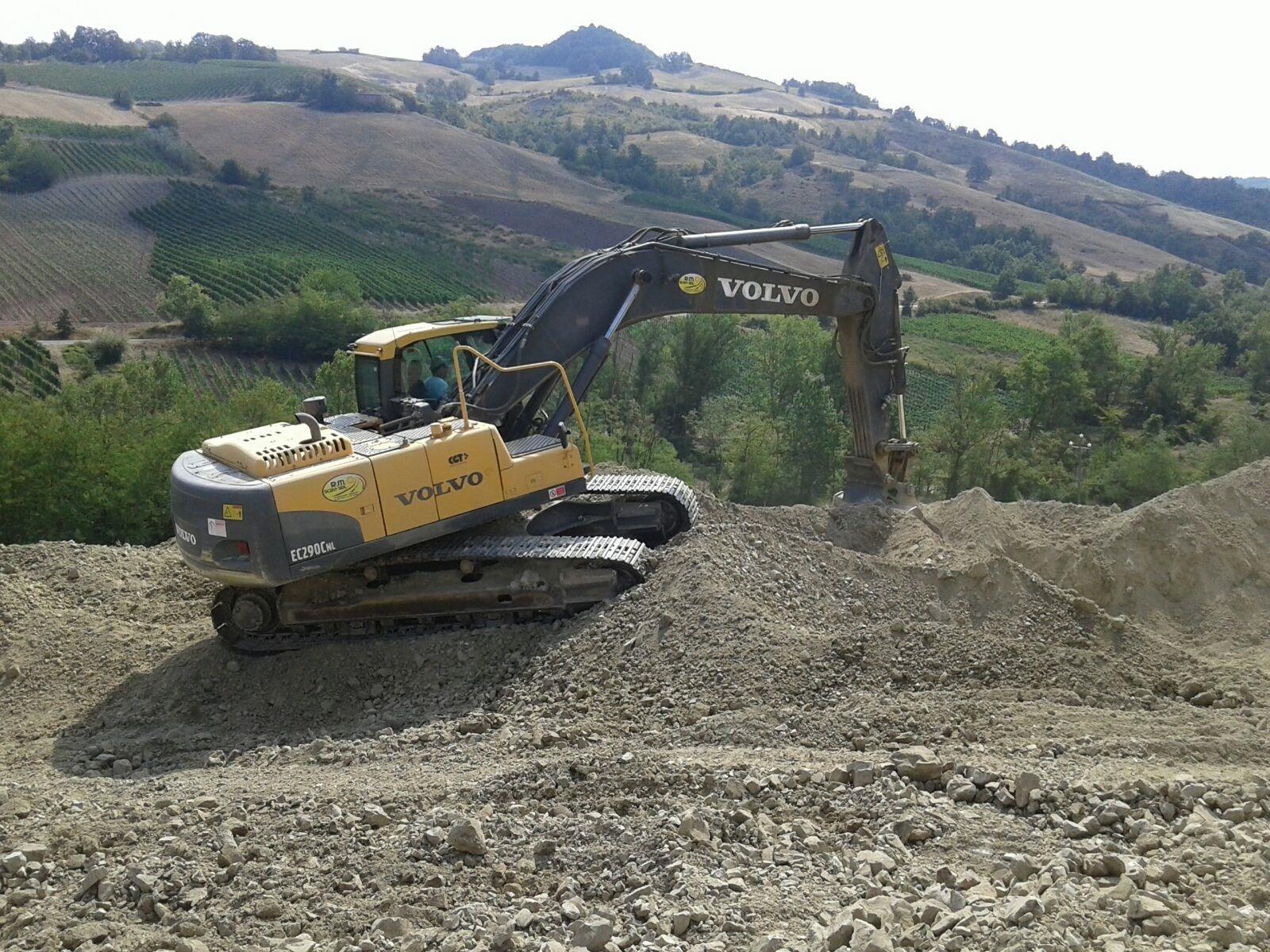 scavatrice con paesaggio di montagna