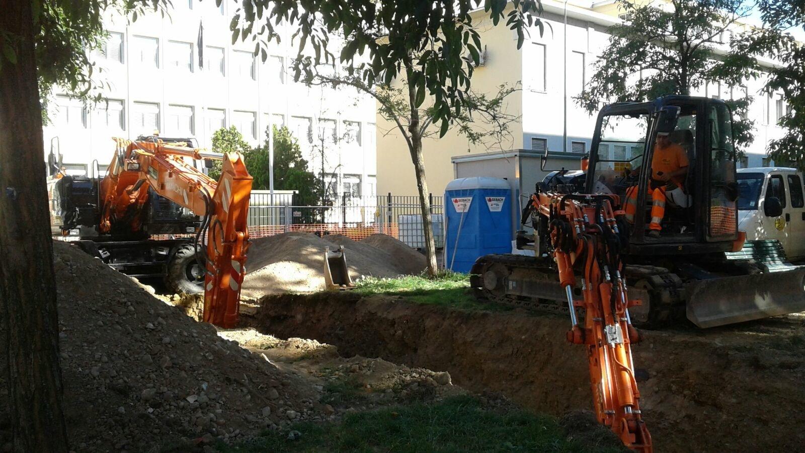 due gru mentre scavano per la costruzione di un impanto fognario