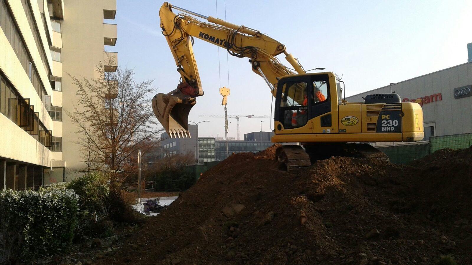 gru gialla sta scavando di fronte a un condominio
