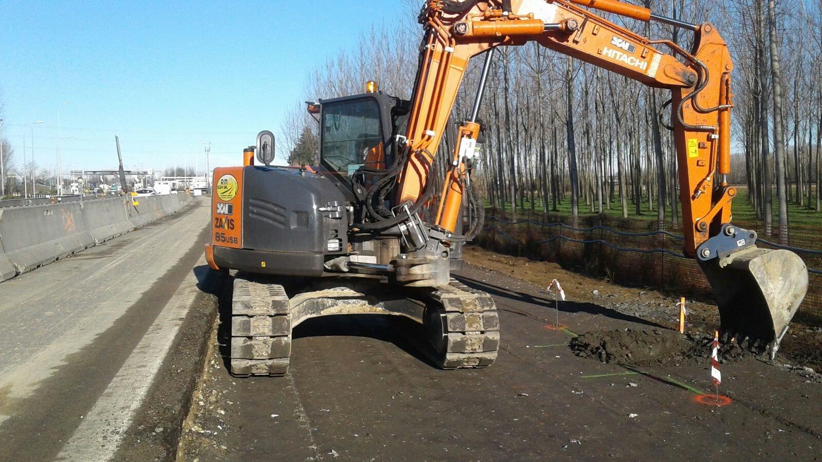 operaio sta scavando con una  gru sul ciglio della strada