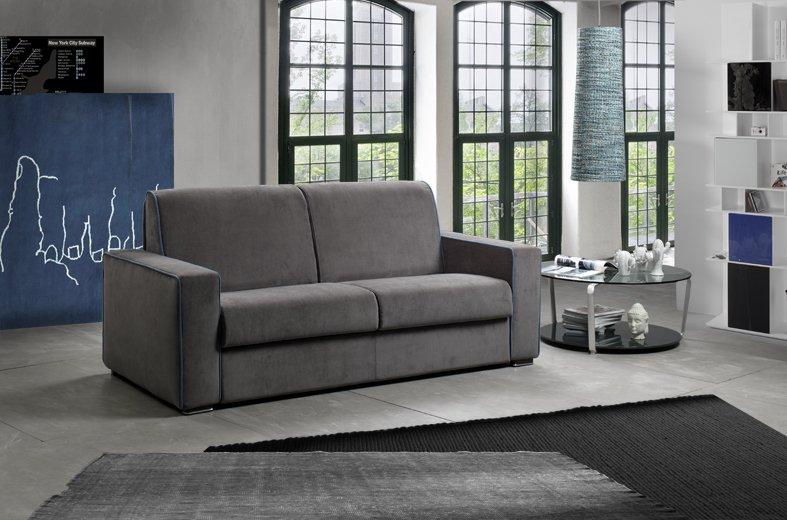 vista interna di una casa con divano grigio, tavolo in vetro e finestre