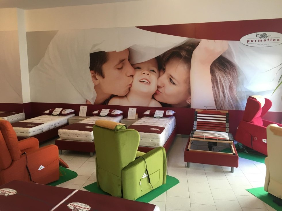 vista di un'immagine di famiglia sulla parete con materassi e poltroni Cagliari Tronu arredamenti permaflex