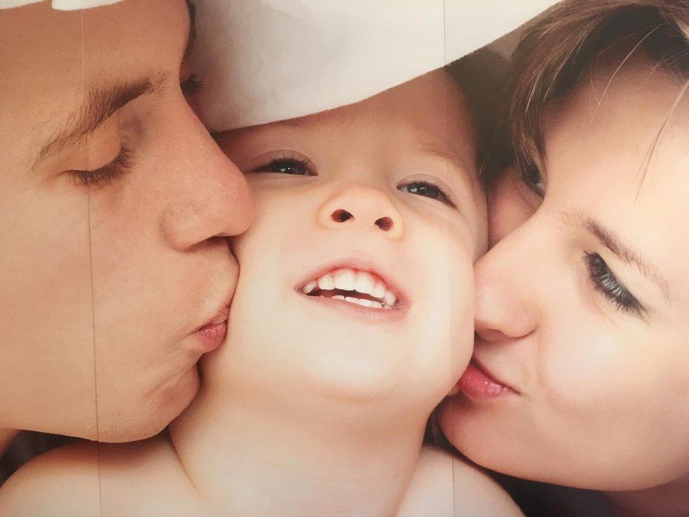 madre, padre e il loro bambino sotto la coperta sul letto di casa