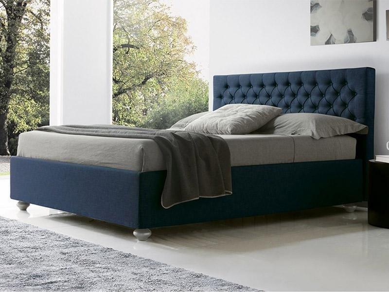 vista angolare di un letto azzurro con materasso grigio e guanciali con ben arredo