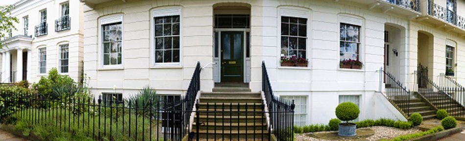 Stone steps with black iron hand rails, leading up to the black front door of a white building