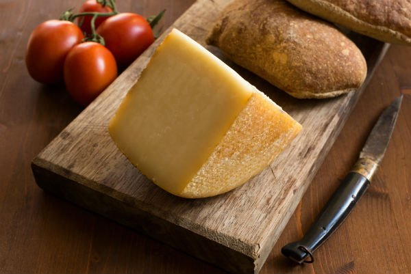 un tagliere con una fetta di formaggio e accanto dei pomodorini