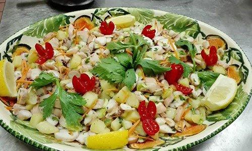 Un piatto con polipo, patate e fette di limone
