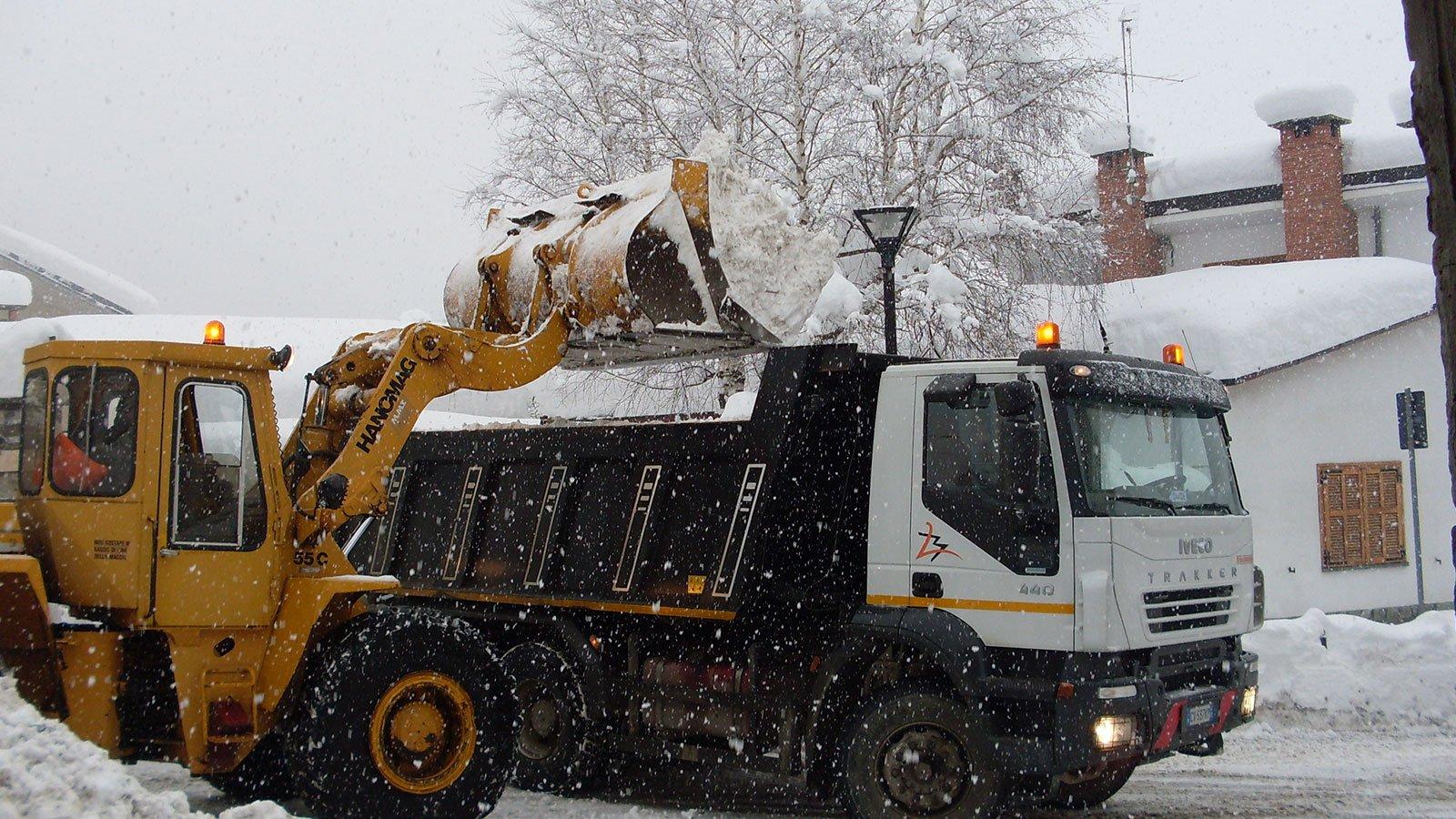 escavatore e camion trasportando neve