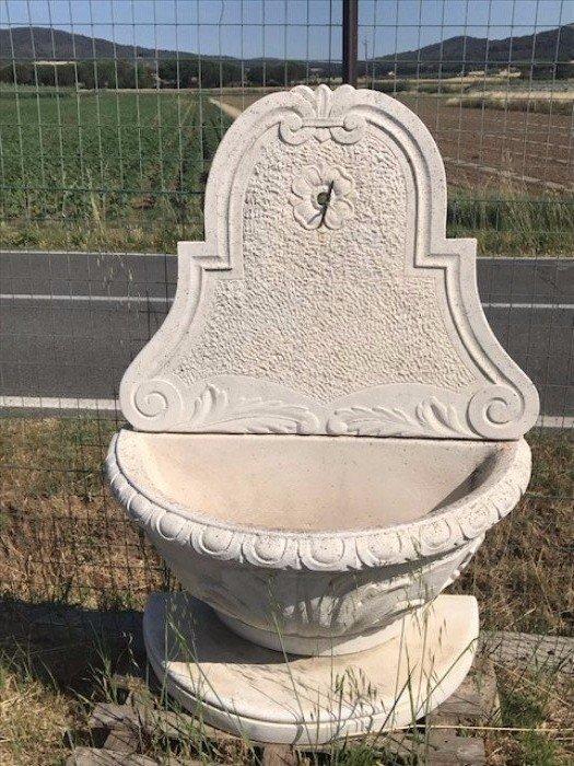 Fonte di parete con caduta in un vaso rotondo