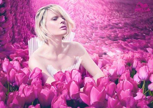una ragazza con capelli corti biondi seduta tra tulipani rosa