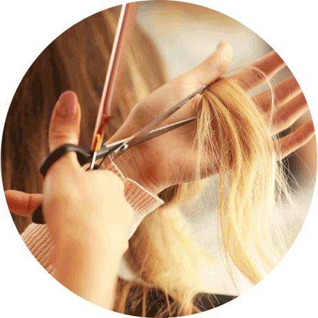 una parrucchiera taglia una ciocca di capelli biondi