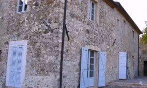 Vecchia casa di pietra con porte e finestre bianche