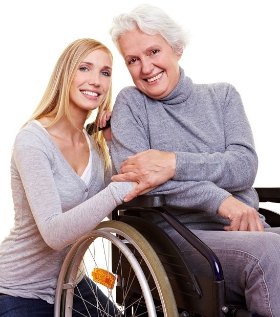 Happy woman sitting in wheelchair with young nurse